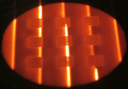 Electron Beam Melting (EBM) powder bed during part building (benchmark cubes) using the electron beam for the pre-heating phase. - Electron Beam Melting (EBM) powder bed during part building (benchmark cubes) using the electron beam for the pre-heating phase.